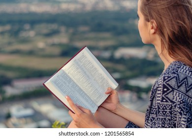 Christian worship and praise. A young woman is reading the bible.