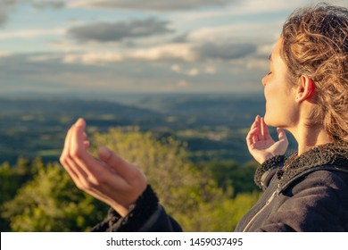 Christian worship and praise. A young woman is praying and worshiping in the evening.