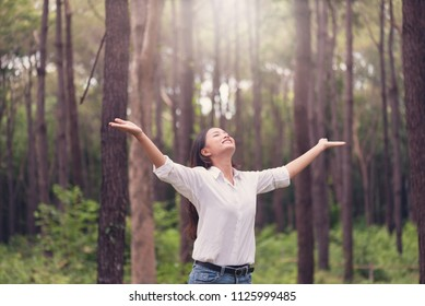 Christian worship with raised hand in pine forest,Happy woman deep breath fresh air in nature breathing clean air. Female enjoying nature and praying to god.