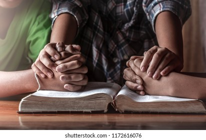 christian young group praying on wooden table with open bible, prayer meeting concept
