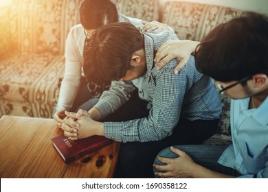A Christian young man  praying for his friends while sitting on wooden chair at home to encourage and support him in his problem , can be use for corona virus crisis concept.