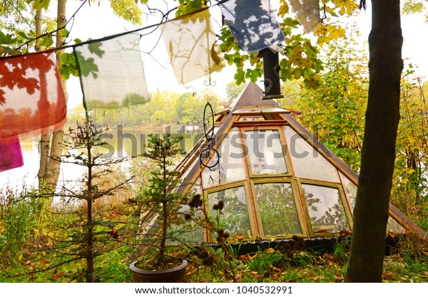 Christiania, Copenhagen/Denmark - October 19, 2012: A pyramid-shaped greenhouse with a lake in the background in the district of Christiania, Copenhagen, Denmark