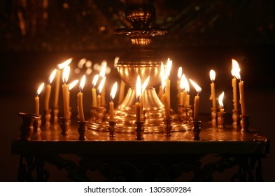 Christianity church interior. Set of lighting candles on dark background