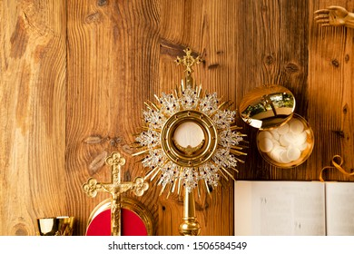 Christianity concept background. Jesus Christ, Bible and golden Christianity symbols composition: The Cross, monstrance, crucifix, chalice, relic. Wooden table. Top view Shot.