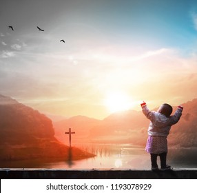 Christianity concept: Child standing in front of cross  background