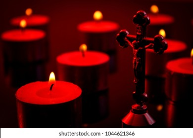 Christianity, faith and religious belief concept with a candlelight scene of a crucifix representing Jesus Christ on the cross and defocused lit candles in the background wit dramatic dark red light