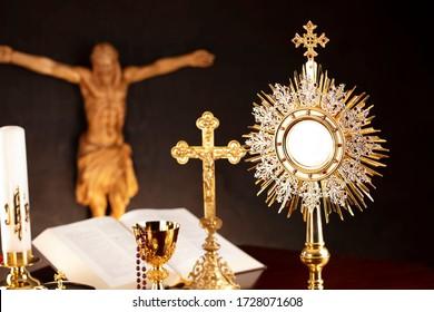 Christianity symbols on dark background. Altar cross, Jesus figure, monstrance, church candle, chalice, rosary, bible.