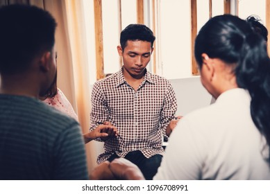 Christians  and Bible study concept. Group of discipleship Studying the Word Of God in church and christians holding each others hand praying together