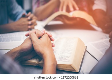Christians are congregants join hands to pray and seek the blessings of God, the Holy Bible. They were reading the Bible and sharing the gospel with copy space.