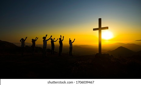 Christians praying to God on the mountain for quick recovery of coronavirus patients with beautiful sunset and cross background