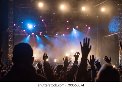 Christians raising their hands in praise and worship at a night music concert