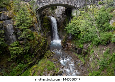 Christine Falls surrounded by greenery under a stone bridge in Mount Rainier National Park, Washington State.