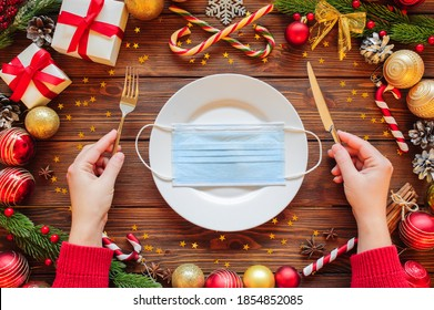 Christmas 2021 new year celebration with table place setting on wooden background with decoration, top view. Female hands put fork and knife. Medical protective mask on a white plate in the center