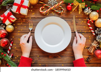 Christmas 2021 new year celebration with table place setting on wooden background with decoration, top view. Female hands put fork and knife.
