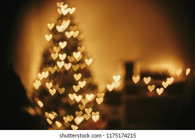 christmas abstract background, beautiful christmas tree golden lights hearts bokeh. blur of yellow glowing illumination in festive room. decor for winter holidays. atmospheric moment