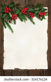 Christmas abstract background border with holly, ivy, cedar cypress and fir on parchment paper over old oak wood.