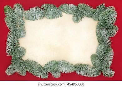 Christmas abstract background border with snow covered blue spruce fir on old parchment paper over red.