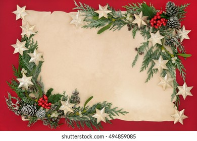 Christmas abstract border with gold star bauble decorations, holly, mistletoe and snow covered cedar cypress on old parchment paper over red background.