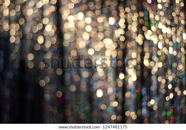 Christmas Abstract Glitter Gold Background. Festive Holiday Glowing Bokeh Backdrop With Tinsel. Blurred Golden Bokeh.