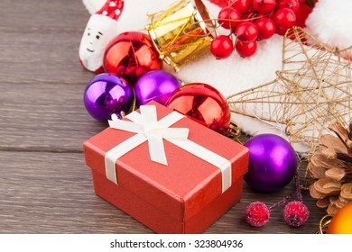 Christmas accessories, hat, balls & box on wooden background