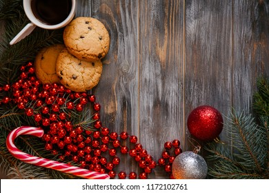 christmas adornment and festive holiday decor. red glittery balls fir tree branch candy cane and bead string on wooden background. top view on coffee and chocolate chip cookie.