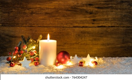 Christmas or Advent candle with red and white christmas ornaments and festive light at snow with wooden background