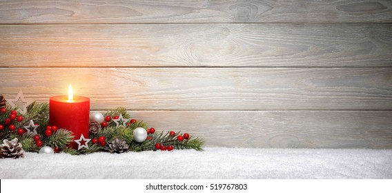 Christmas or Advent wood background with a burning candle on snow, decorated with fir branches and ornaments, panoramic format with copy space