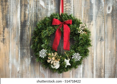 Christmas aged wood background. Traditional pine xmas decoration at brown wooden door or wall. Pine Christmas wreath decorated with toys, red ribbons hanging in home interior. Horizontal colour photo.