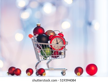 christmas alam clock and shopping cart with fairy lights on background