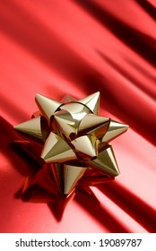 christmas ambiance with golden cockade on red parcel paper