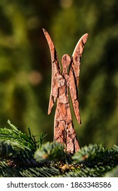 A Christmas angel made of wood isolated behind a pine branch and in front of a natural green background