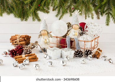 Christmas angels and Christmas balls in basket, Christmas tree on white wooden background