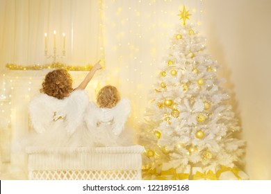 Christmas Angels looking to Xmas Tree, Children with Wings Back View Pointing to Lighting Star
