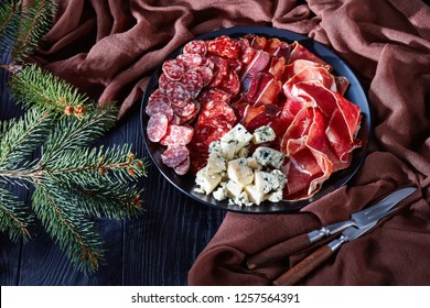 christmas antipasti - cheese, sausages and dry cured meat - jamon,  chorizo, blue mold cheese, sliced fuet sausages on a plate on a table with fir tree, view from above, close-up