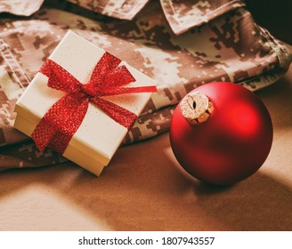 Christmas in the army. Red xmas ball and gift box on US America military uniform, closeup view
