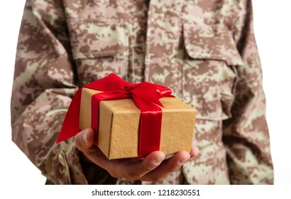 Christmas and Army. Young soldier holding a christmas gift standing on white background