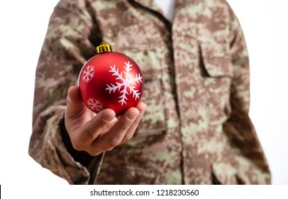 Christmas and Army. Young soldier holding a red christmas ball standing on white background