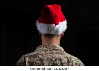 Christmas and Army. Young soldier wearing santa hat standing on black background