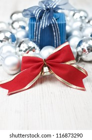 Christmas arrangement with baubles, gift box and red bow against white wooden table.
