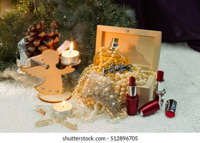Christmas arrangement with wooden box filled with a pearl necklace with perfume, spruce branches, candles, angels and lipstick.