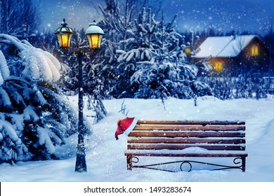 Christmas art card. Santa hat on a bench in the snow against the background of the Christmas winter forest. Village house in the background. Wonderland.