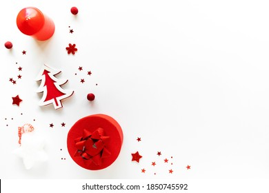 Christmas art composition with red decor, gift box and candle on white. Chritmas eve, noel, gift concept. Flat lay, top view, above, copy space