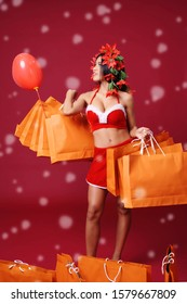 Christmas asian woman wearing santa red dress costume holding shopping bags standing on red background with snow fall.