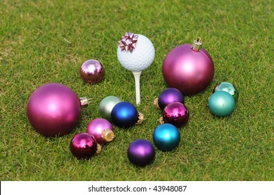 Golferâ??s Christmas with assortment of ornaments surrounding and on a Golf Tee.  Focus is on the ornament on the golf tee.