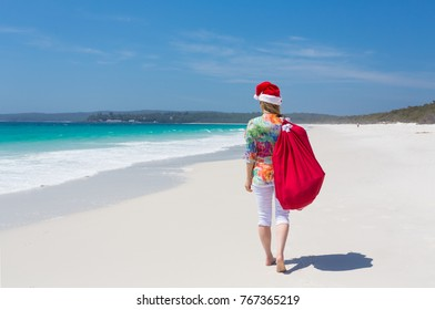 Christmas for a lot of Australians means hot summer sunshine and days spent at the beach.  A woman wearing a santa hat strolls along a white sandy beach with a red drawstring sack.   Space for copy