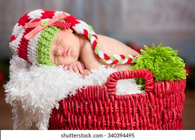 Christmas Baby.  Adorable newborn fast asleep in a red basket and wearing a long read and white striped hat.