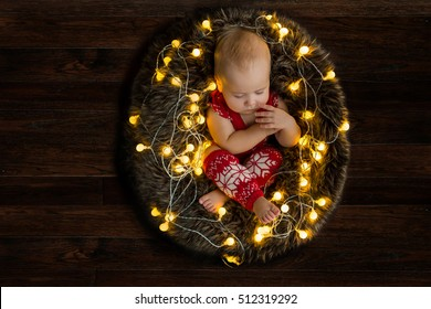 christmas baby sleeping in fur nest with lights on dark wooden background holidays inspiration