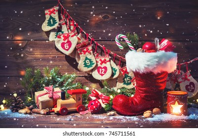 Christmas background. Advent calendar and Santa's shoe with gifts on rustic wooden table