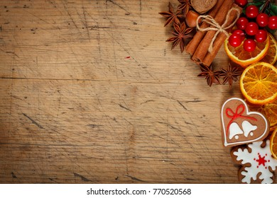 Christmas background - anise, cinnamon, gingerbread and sliced orange on wooden table