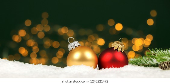 Christmas background - christmas balls and pine branches in the snow with blurred lights in the background